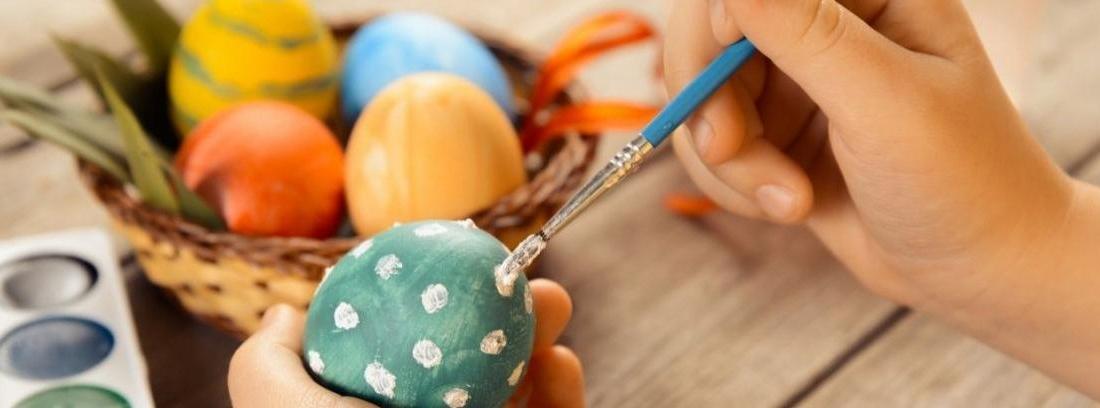 Una niña pinta un huevo con colores y pincel