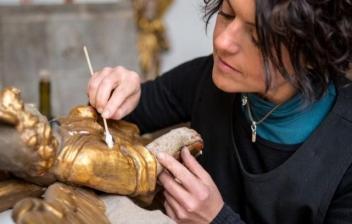 Mujer restaurando una pieza de metal antiguo