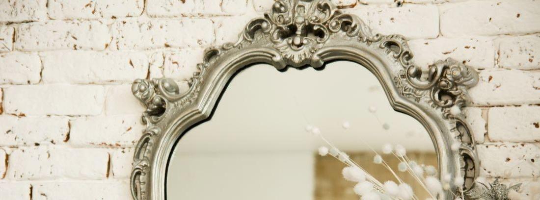 Una habitación con un espejo ovalado en la pared una mesa con diversos objetos y un reloj de pared a