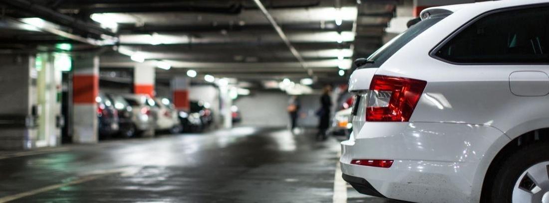 Dos coches aparcados con una plaza vacía entre ambos