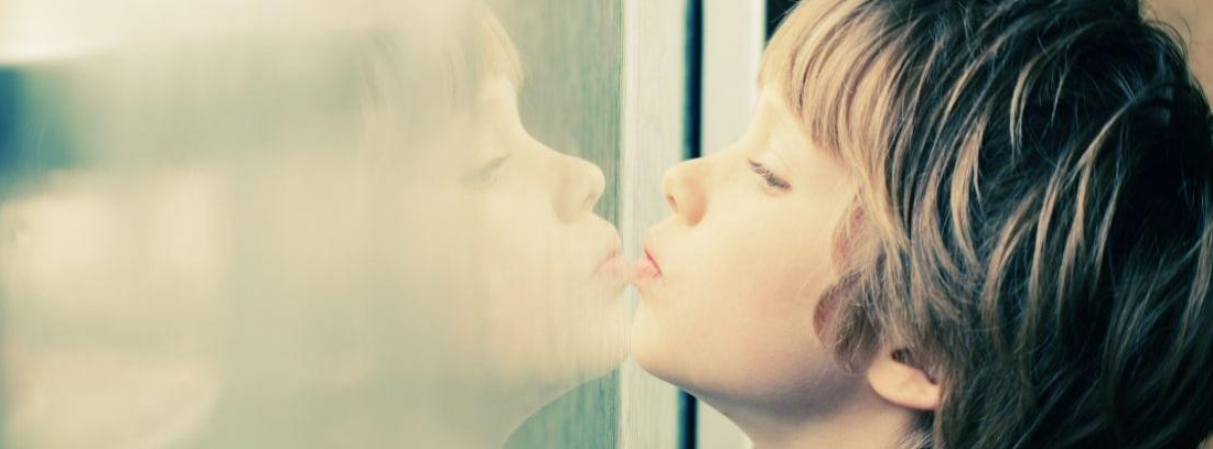 Niño mirando por la ventana esperando a sus padres