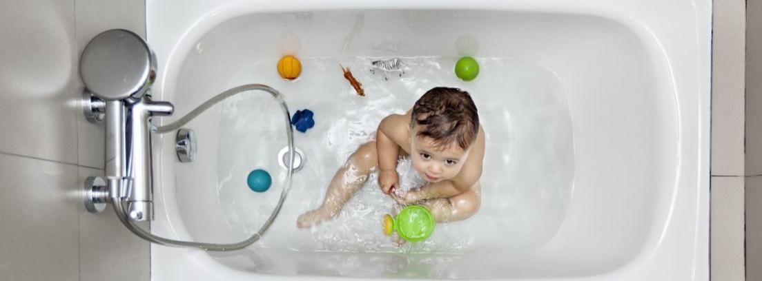 Bebé dentro de una bañera con juguetes de baño