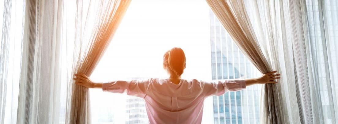 mujer abriendo cortinas