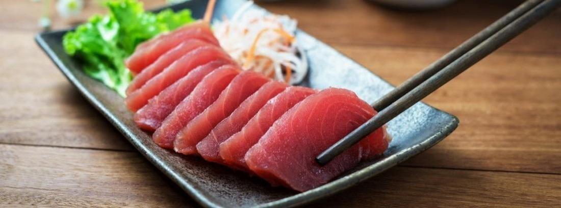 Filete de atún crudo sobre una tabla de madera y un trozo de limón