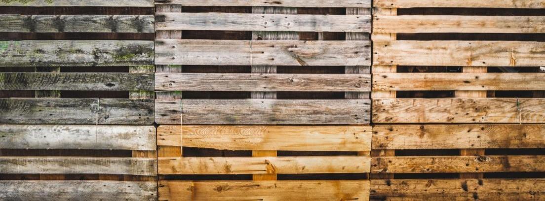 Pared forrada de palés de madera de diferentes tonos  y color.