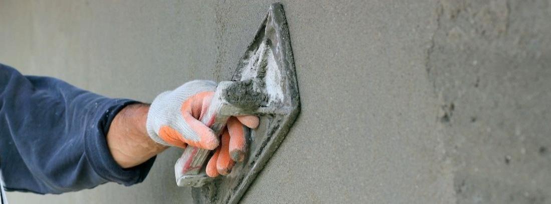 un obrero con espátula para estucar las paredes