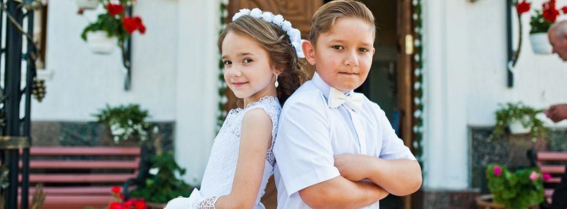 Niña con traje largo blanco frente a niño con traje de chaqueta beige