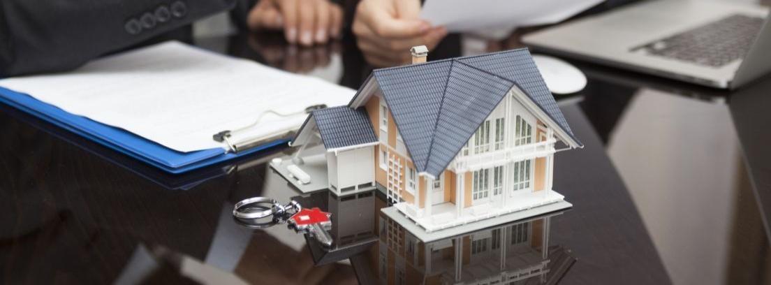maqueta de una casa sobre una mesa con una llaves al lado