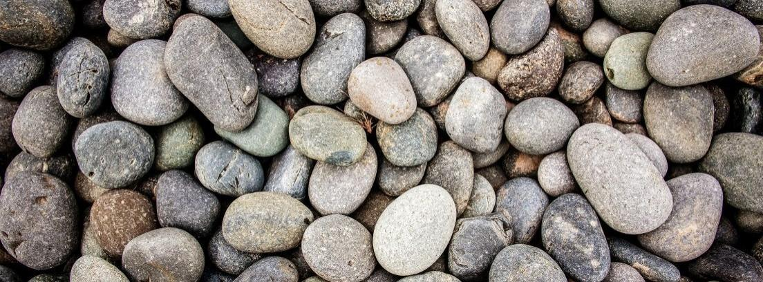 Una mano sujeta 4 piedras blancas que tienen escrito LOVE