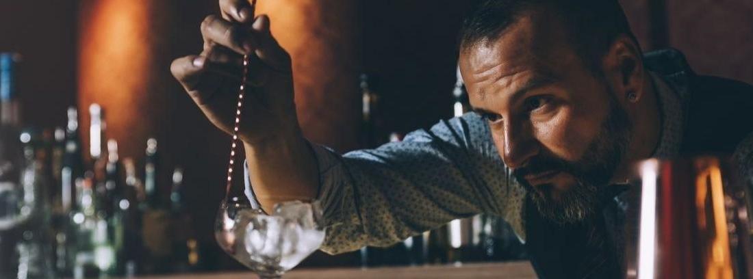 Barman decora un cóctel con una rama verde