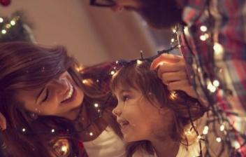 Familia decorando un árbol con adornos de Navidad originales