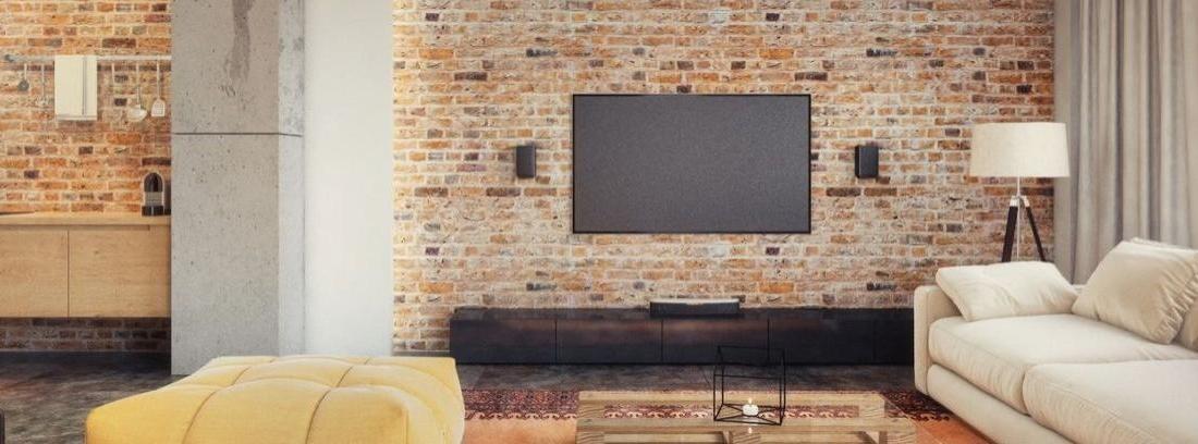 Pantalla de televisión en una pared de ladrillo sobre un mueble de madera.
