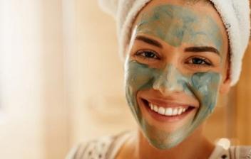 Mujer sonriente sujetando tres brochas de maquillaje