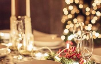 Plato blanco sobre plato gris y servilleta con cubiertos de bronce con adorno navideño