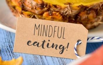 Fondo de diferentes verduras y hortalizas con un cartel en forma de corazón que señala Mindful eatin