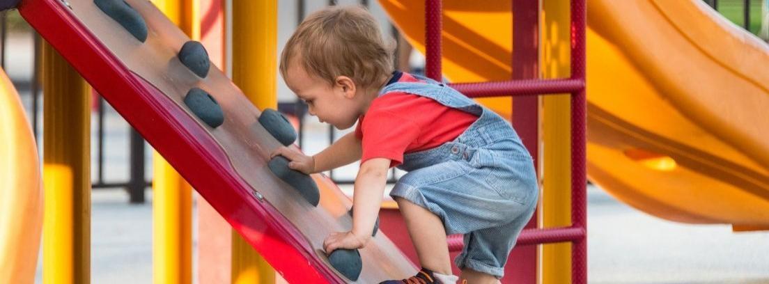 Niño con camiseta roja y peto vaquero subiendo a un tobogán
