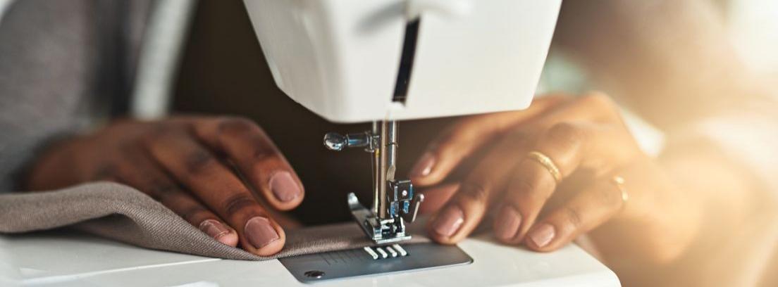 Unas manos cortan una tela con unas tijeras