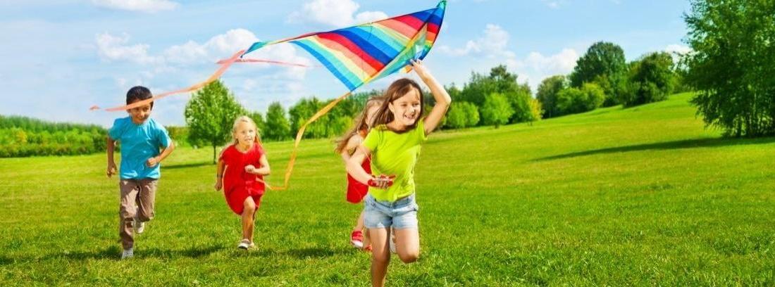 4 niños al aire libre se abrazan y ríen