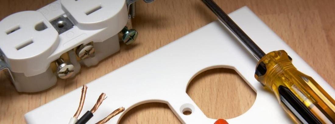 Primer plano de unas manos con un destornillados trabajando en un enchufe