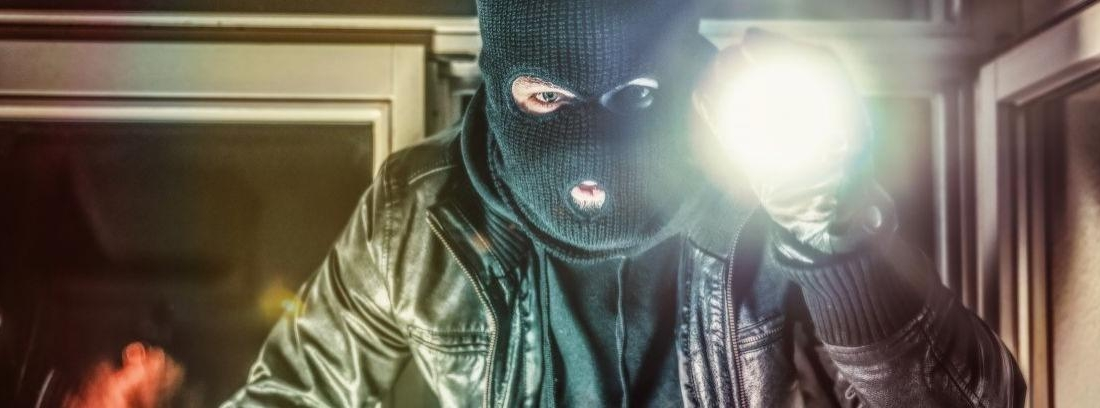 Hombre con pasamotnañas negro y gesto asustado alumbrado por un foco de luz