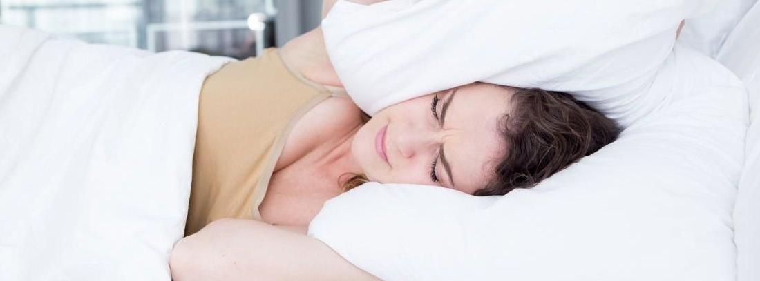 mujer tapándose los oídos con una almohada por causa del ruido