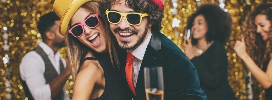 Copas de champagne con un reloj de fondo a punto de marcar las doce y adornos navideños en color oro
