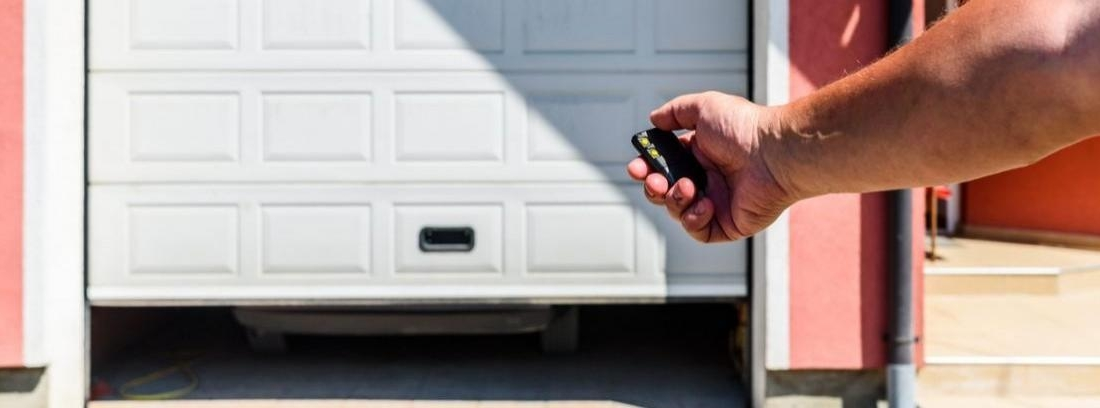 Puerta de garaje automática y enrollable medio abierta dejado ver un coche con los faros encendidos