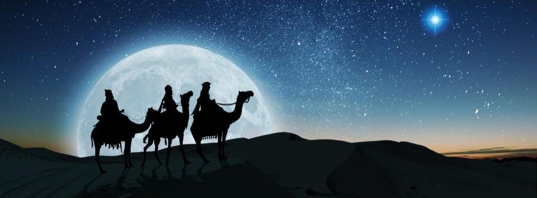 Dos niños agachados a los pies de un árbol de Navidad miran unos paquetes envueltos en papel de rega