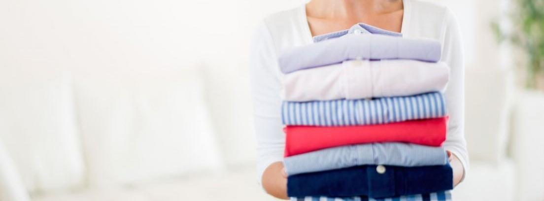 Mujer llevando camisas planchadas
