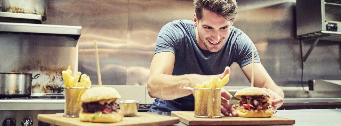 Un hombre y un niño en una cocina con un delantal ríen juntos.