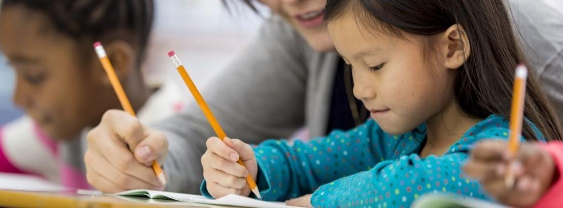 Niños en una mesa escribiendo sobre un cuaderno