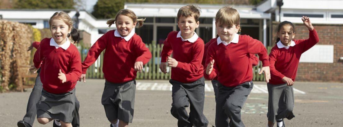 Varios niños con uniforme escolar corriendo