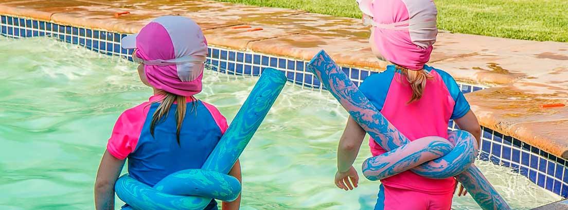 Dos niños al borde de una piscina con churro flotador azul atado a la cintura.