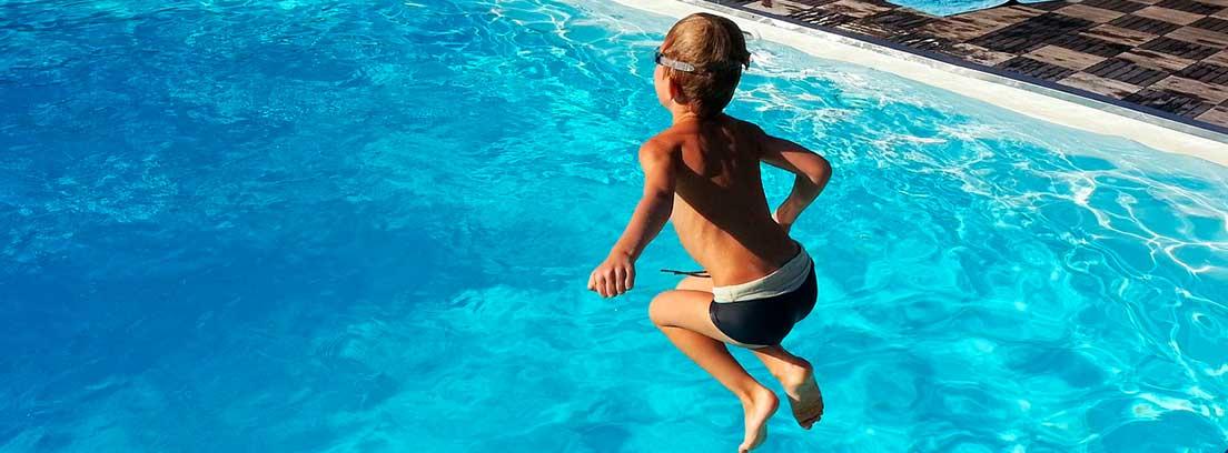 Niño con gafas de bucear y bañador negro en el aire sobre piscina de agua azul