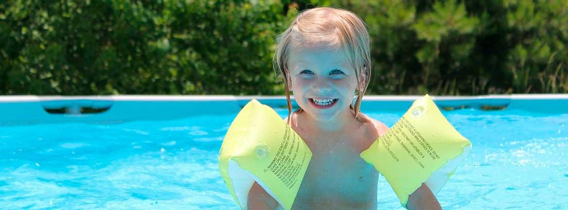 Niña flotando sobre agua de piscina con manguitos amarillos en los brazos