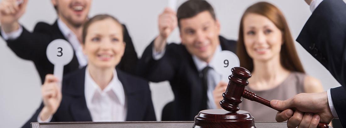 Varias personas levantan una paleta blanca con un número en una subasta. Enfrente de ellos una persona de traje golpea con un mazo sobre la mesa.