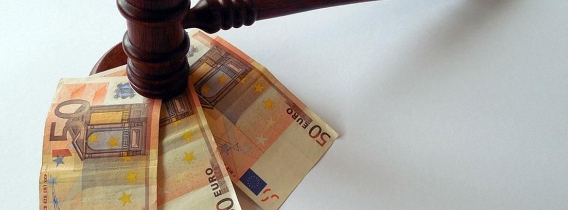Un mazo de madera golpea tres billetes de 50 euros