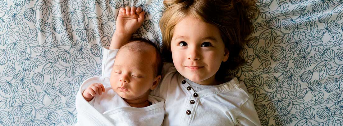 Vista cenital de un bebé y una niña sonriente tumbados boca arriba