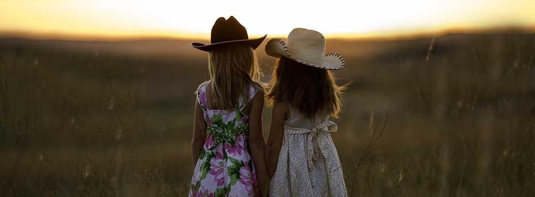 Dos niñas de espaldas con vestidos y sombreros de paja dándose la mano en un campo de trigo