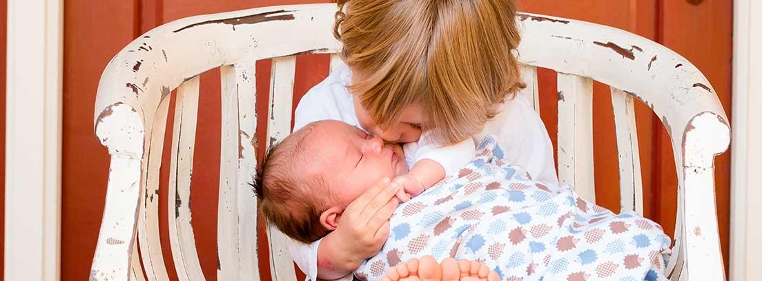 Niño sentado en un banco de madera blanco con un bebé en brazos al que le da un beso
