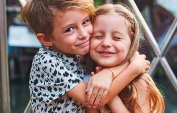 Niño y niña sonrientes sentados y abrazados