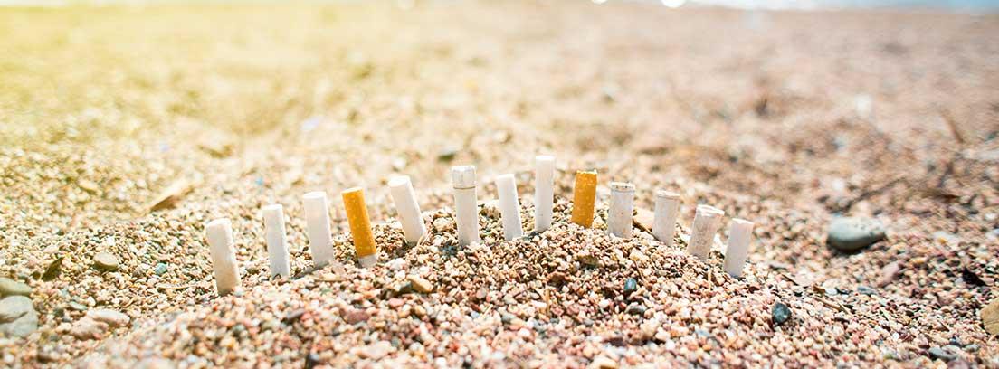 Varias colillas alineadas en la arena de una playa.