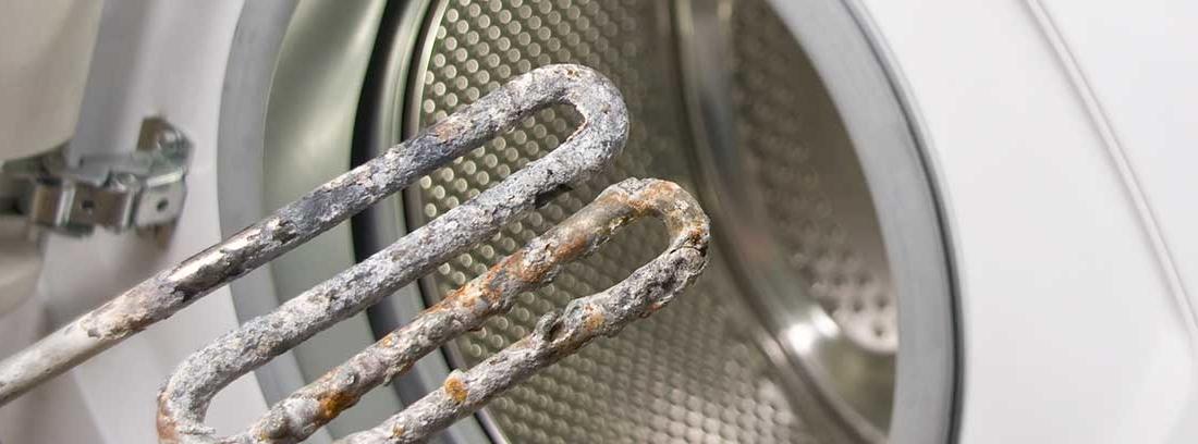 Pieza de la lavadora comida por la cal del agua