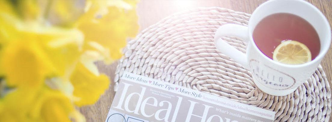 Revista de decoración sobre madera y junto a taza de té con rodaja de limón
