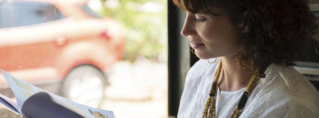 Mujer con camisa blanca y collar mira hacia revista que sujeta abierta entre sus manos
