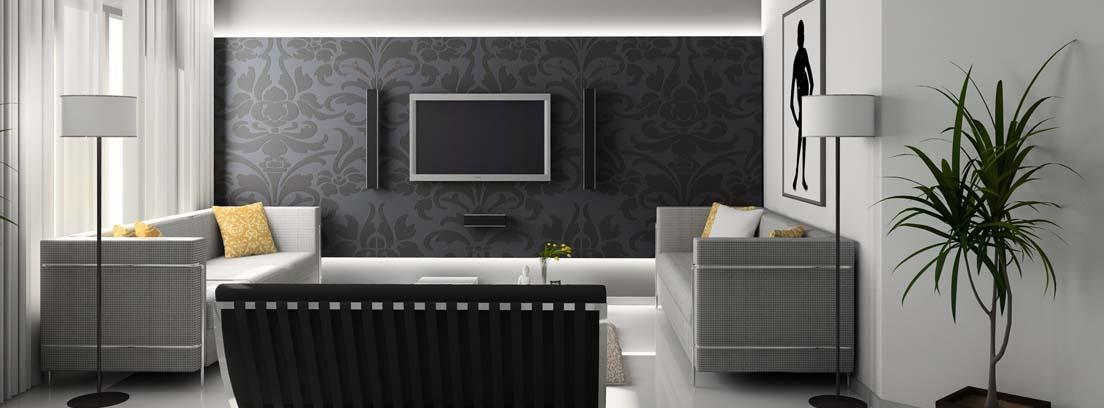 Habitación con sofás grises y gran tele colgada en pared del fondo.