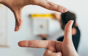 dos manos formando un rectángulo con dedos delante de una pared blanca