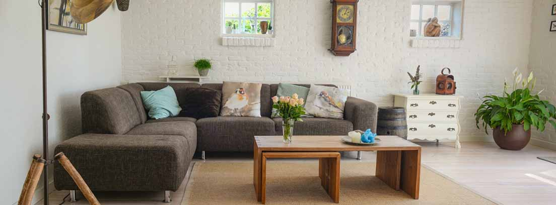 Estancia de con sofás en rinconera grises y pequeñas mesas de madera delante.