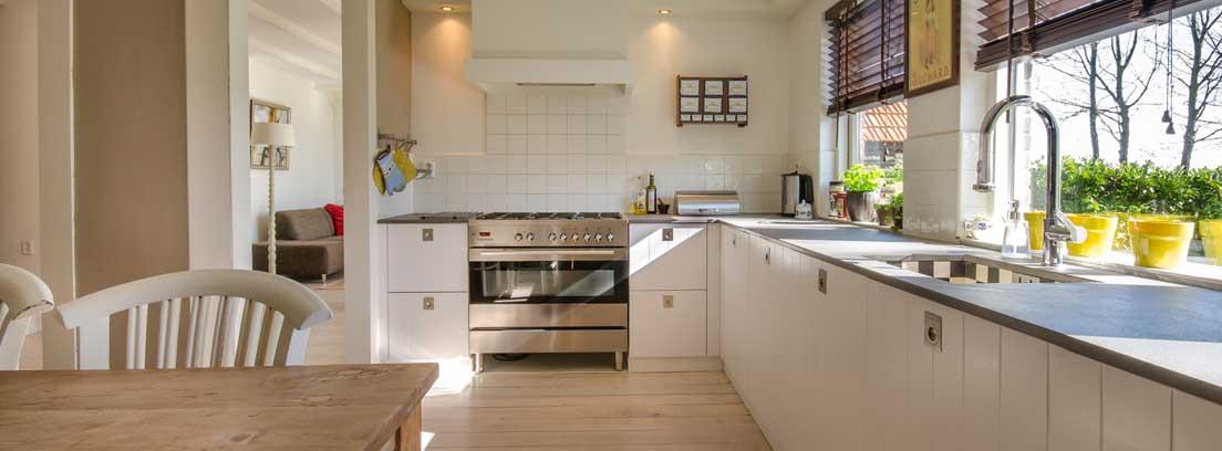 Cocina con muebles blancos, suelo de madera y dos grandes ventanas.