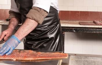 Hombre con delantal negro y guantes azules con cuchillo en la mano sobre un salmón.